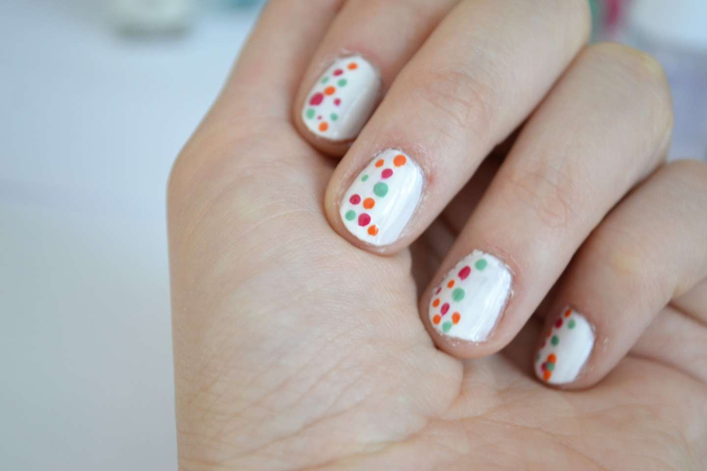 Nail art bianca con pois colorati