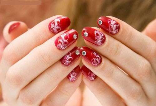 Nail art rossa con decorazioni e strass