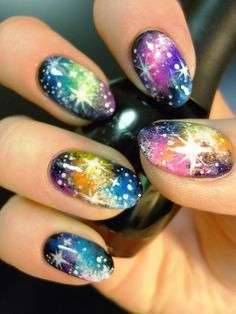 Nail art multicolor con stelle e pianeti