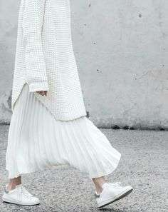 Maxi pull e gonna a pieghe con sneakers