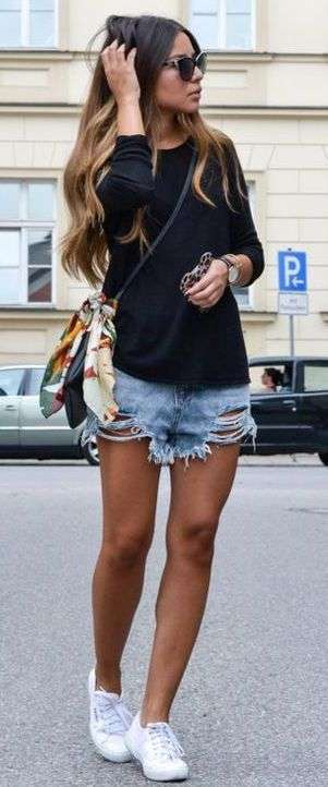 Look con sneakers, shorts e blusa nera